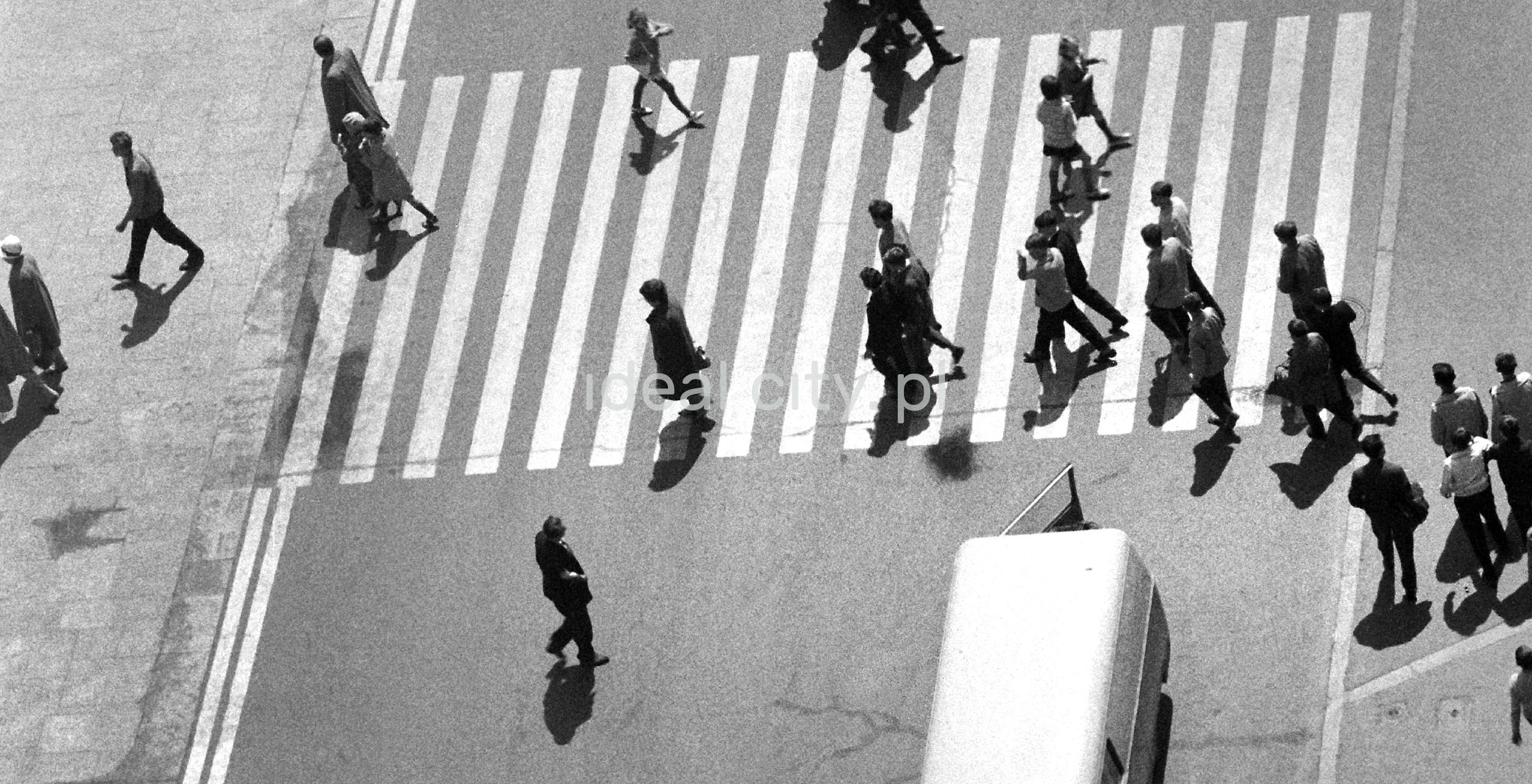 Ujęcie z góry na sylwetki osób przechodzących przez przejście dla pieszych, tuż przy nim widoczny tył mikrobusa z otwartymi tylnymi drzwiami.