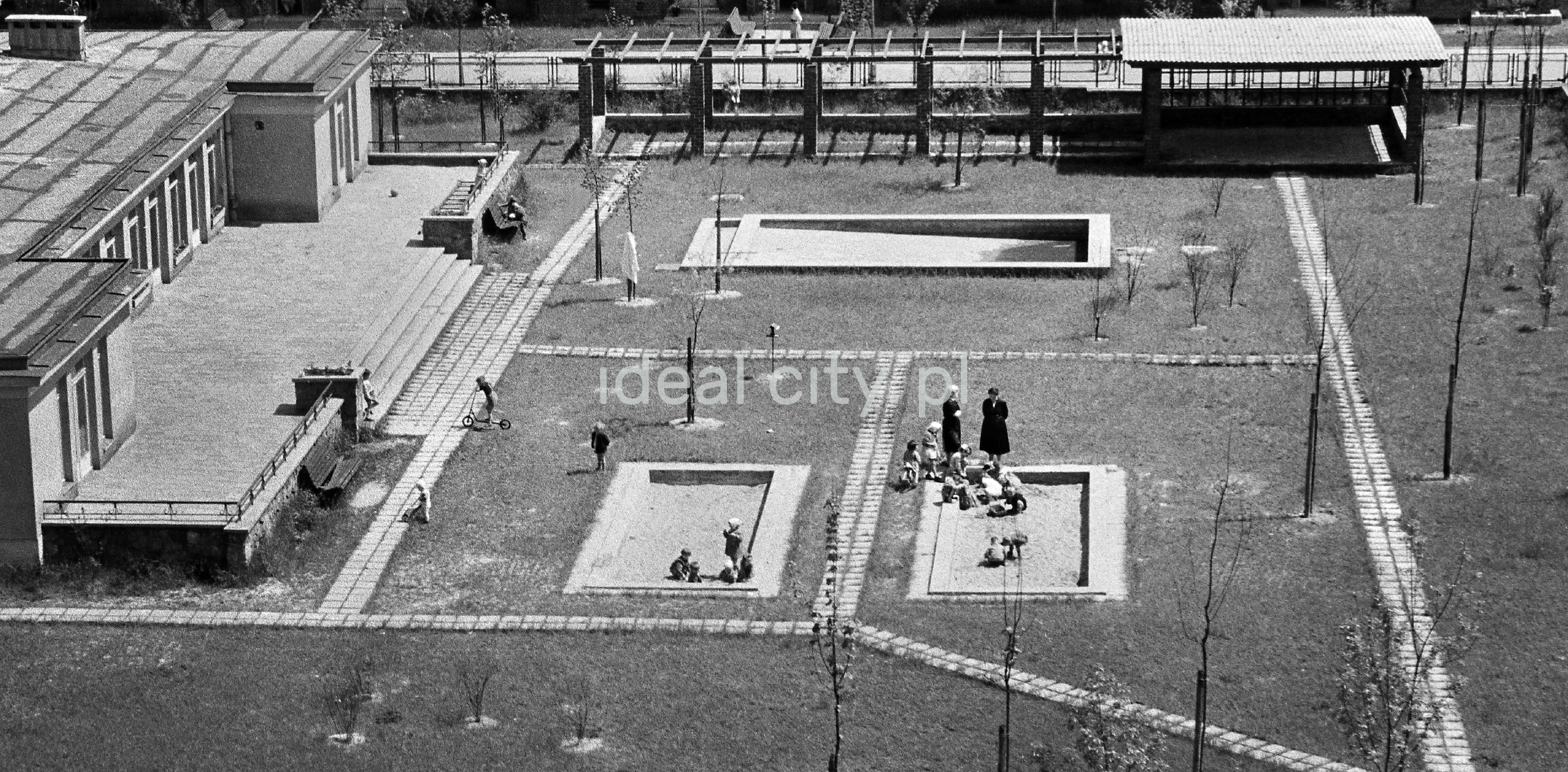 Widok z góry na zorganizowany plac zabaw przed przedszkolem, widoczne bawiące się dzieci oraz opiekunki.