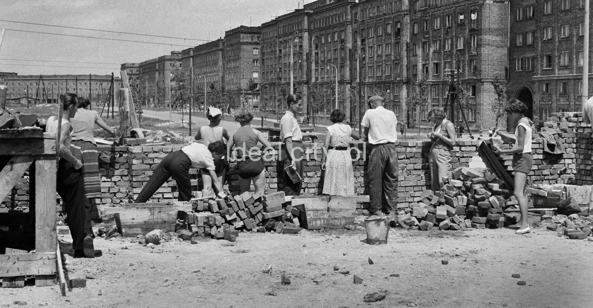 Grupa kobiet i mężczyzn w koszulach pracuje wzdłuż niewysokiego muru, w tle zabudowa mieszkalna.