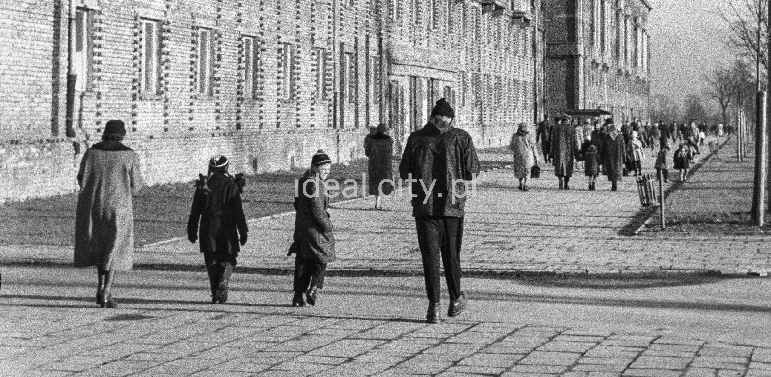 Perspektywiczne ujęcie na ruch pieszy na szerokim chodniku. Przechodnie w zimowych ubraniach, po lewej ciąg zabudowy mieszkalnej.