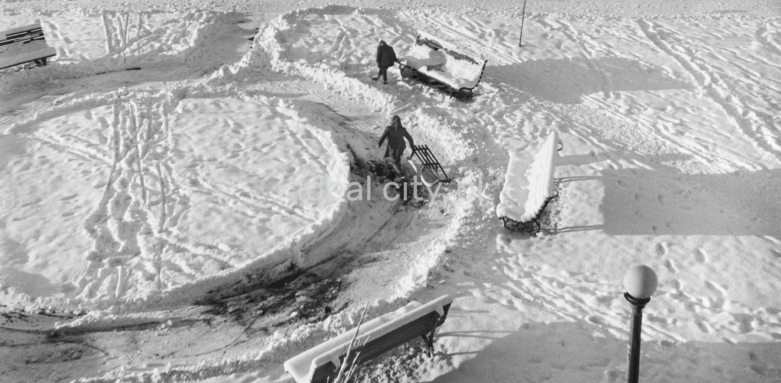 Ujęcie z okna na zaśnieżone alejki, dzieci z sankami, ławki.