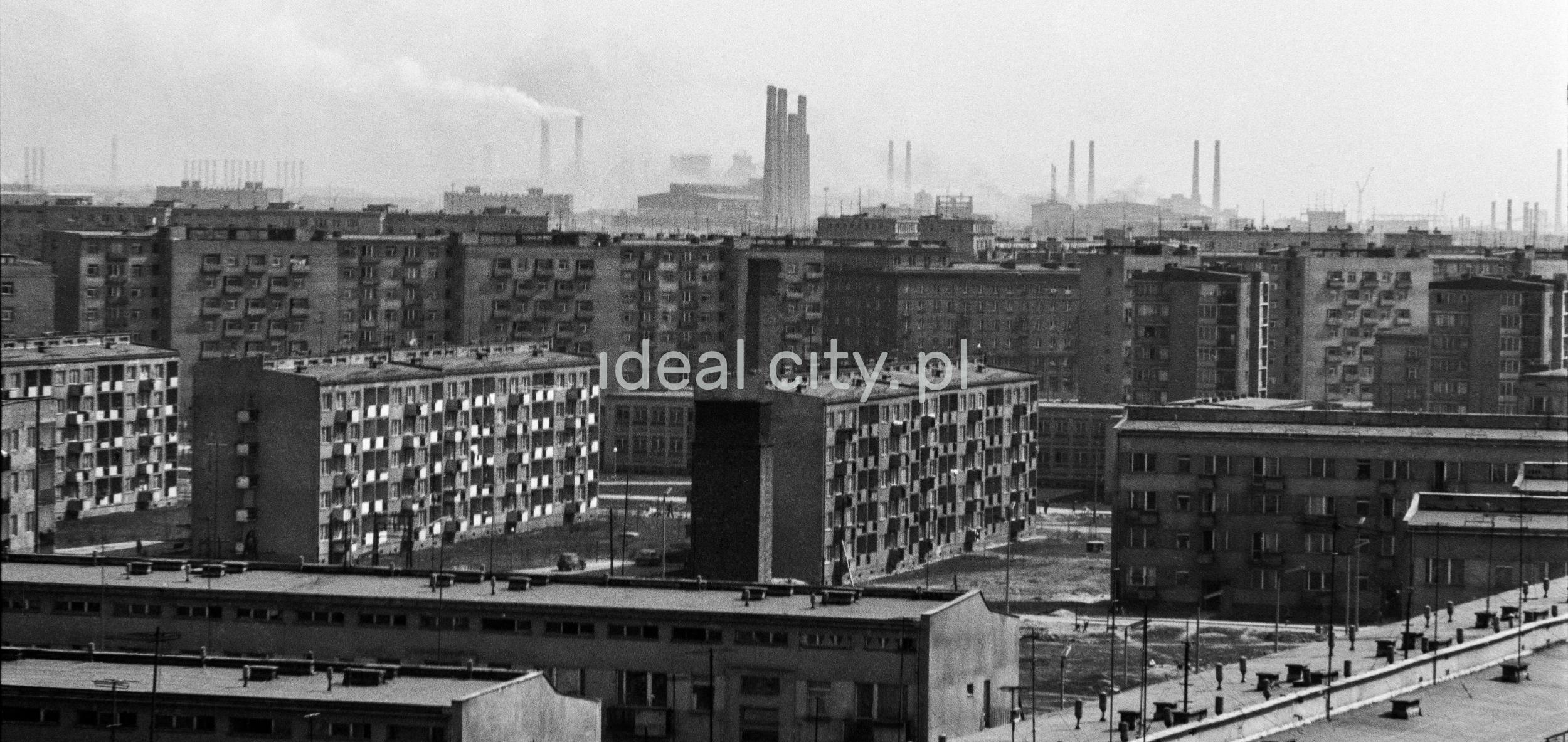 Perspektywiczne ujęcie na osiedla bloków mieszkalnych, linięhoryzontu zamykają kominy fabryczne.