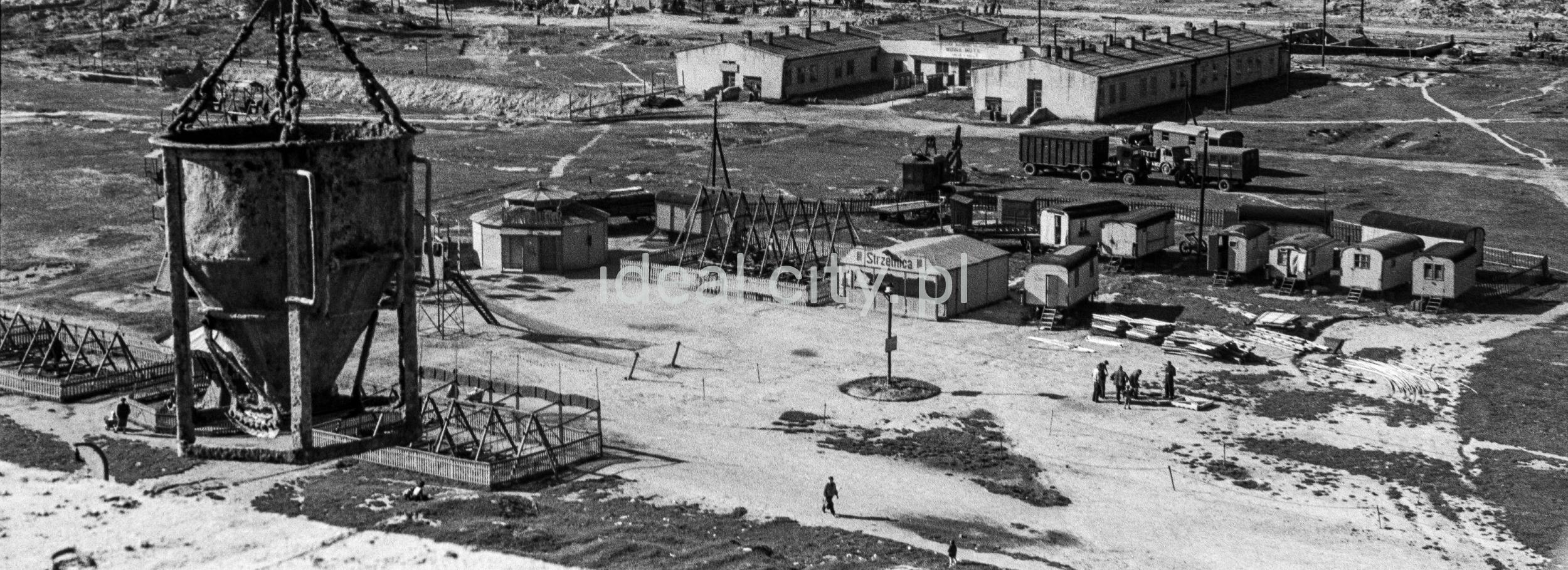 Widok z góry na plac zagospodarowany barakami wesołego miasteczka na przemian z administracyjnymi. Na pierwszym planie gruszka budowlana.