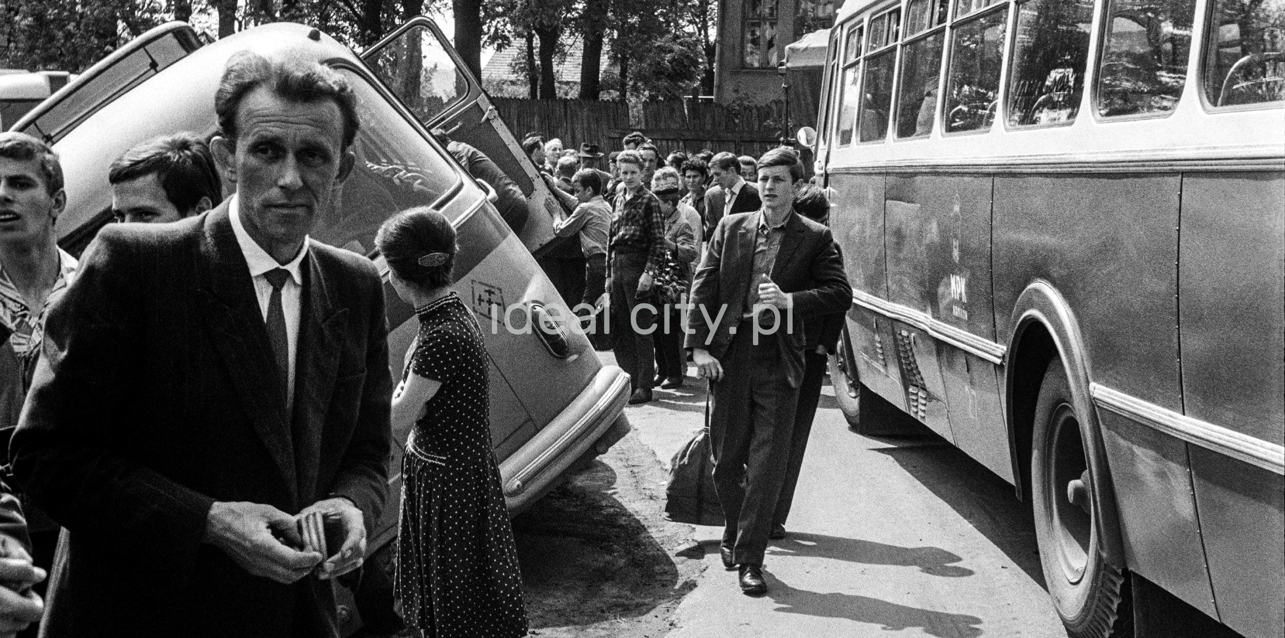 """Mężczyzna przechodzi pomiędzy dwoma autobusami typu """"ogórek"""", jeden z nich leży w rowie, dookoła gapie."""
