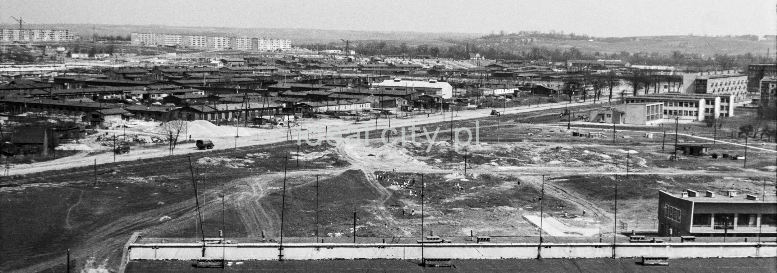 Perspektywiczne ujęcie z góry na łąkę wypełnioną kilkudziesięcioma barakami, na horyzoncie zabudowa blokowa.