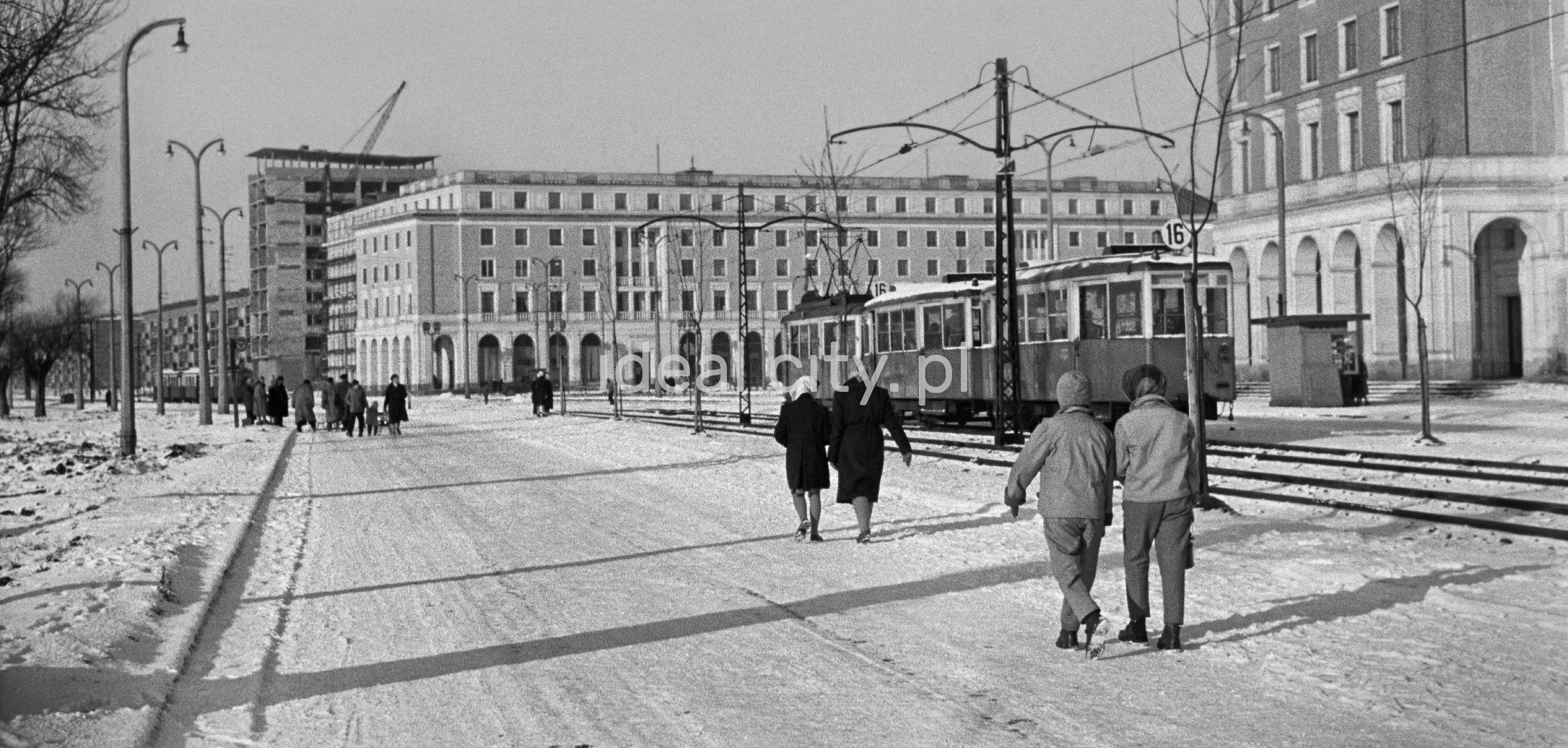 Ruch pieszy na zaśnieżonej ulicy, w tle monumentalna zabudowa mieszkalna.