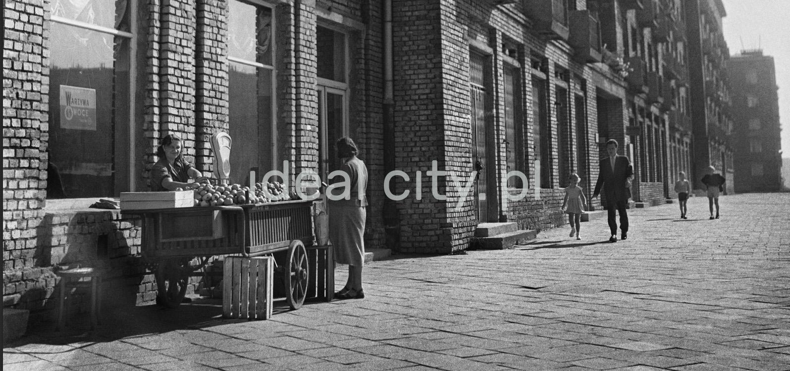 Stoisko na chodniku przed sklepem warzywnym ulokowanym na parterze budynku z cegły. Na szerokim chodniku przechodnie.