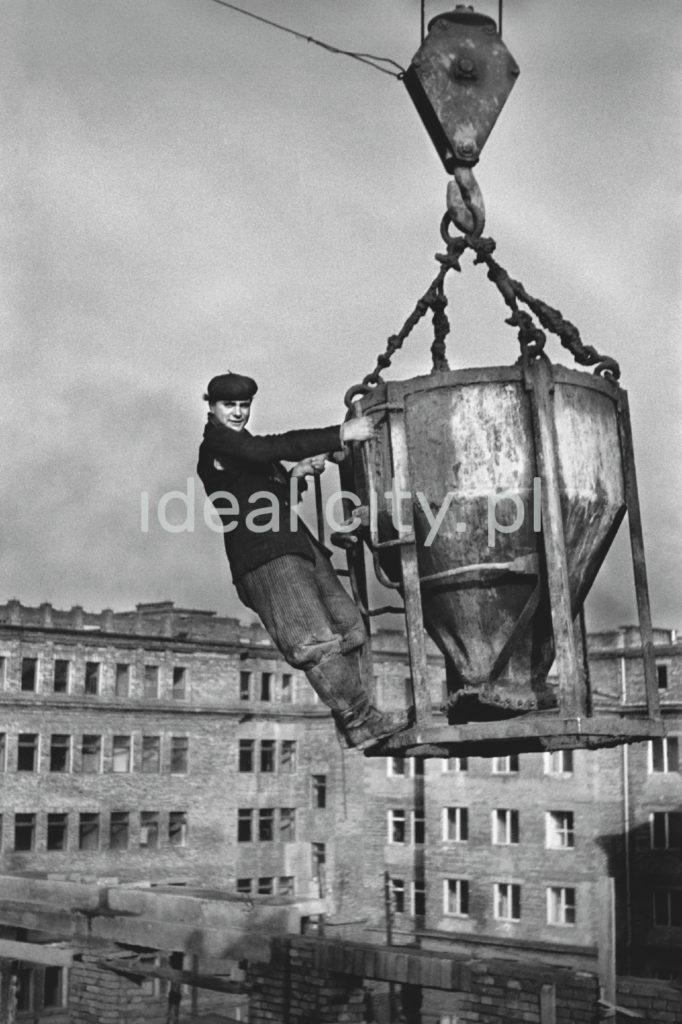 Pracownik w kufajce wisi na wysokości wraz z gruszką na beton.