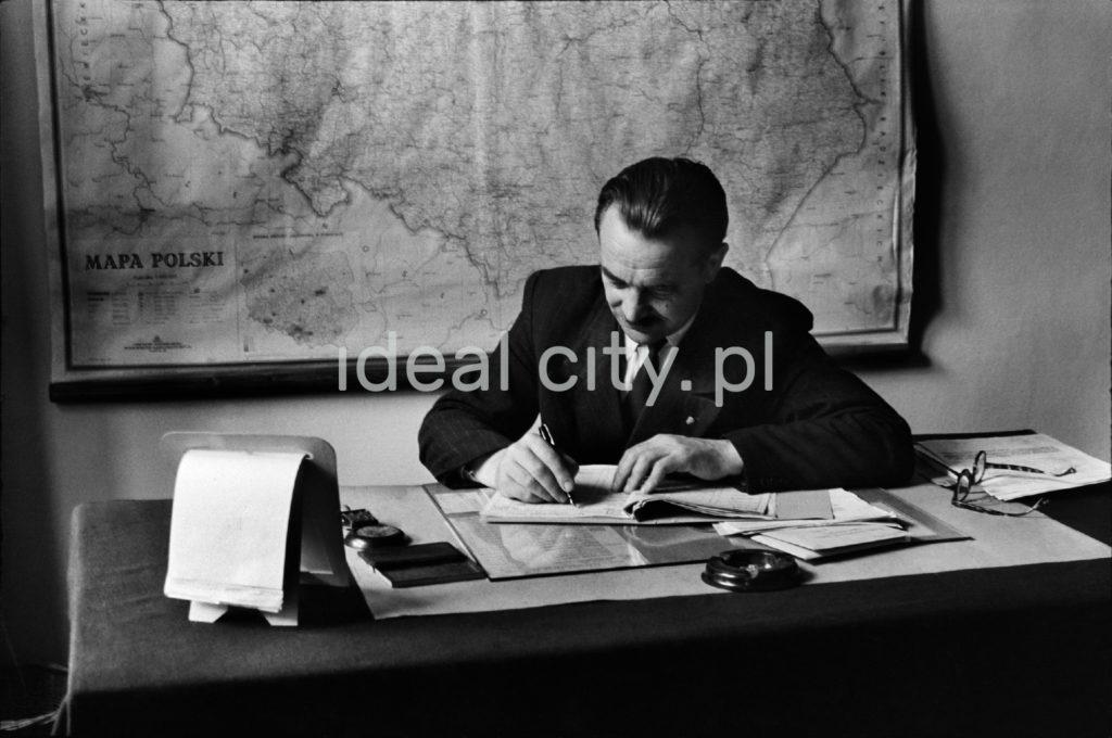 Mężczyzna w garniturze przy biurku zapisuje coś w dokumentach.
