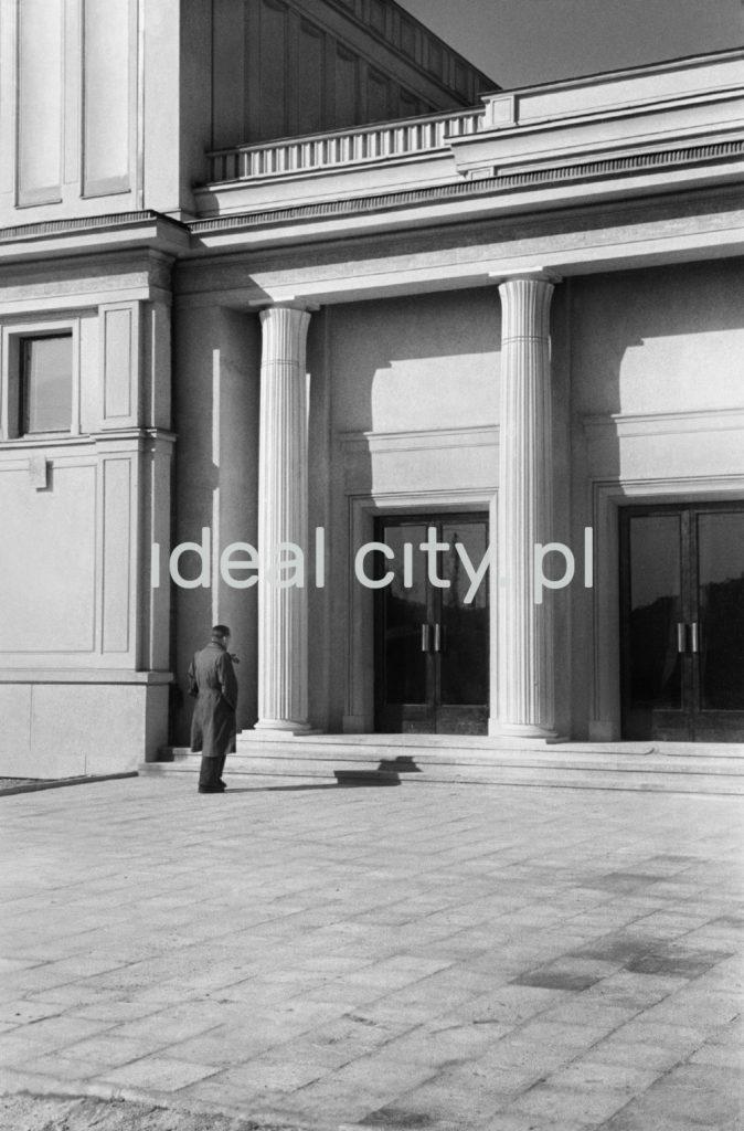 Mężczyzna w płaszczu przed monumentalnym wejściu do budynku.