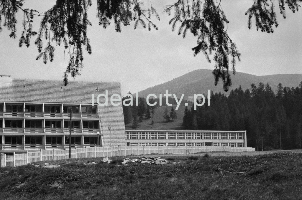 Pocztówkowe ujęcie przedstawia obsutronnie spadziste budynki kompleksu wypoczynkowego, w tle góry.