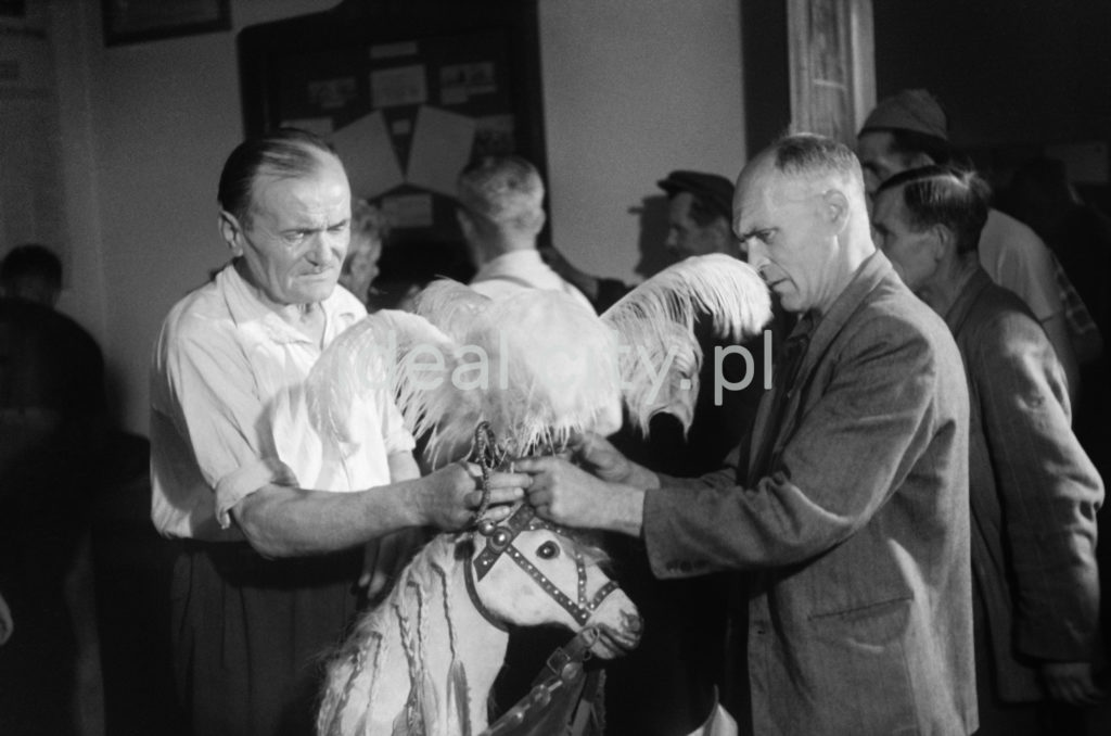 Dwaj mężczyźni poprawiają strój w postaci głowy konia z piuropuszem.