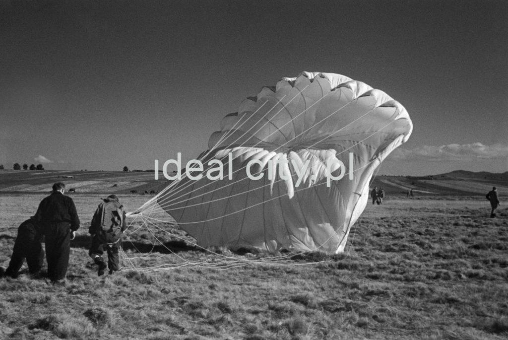 Spadochroniarz z rozwiniętym spadochronem na murawie lotniska.