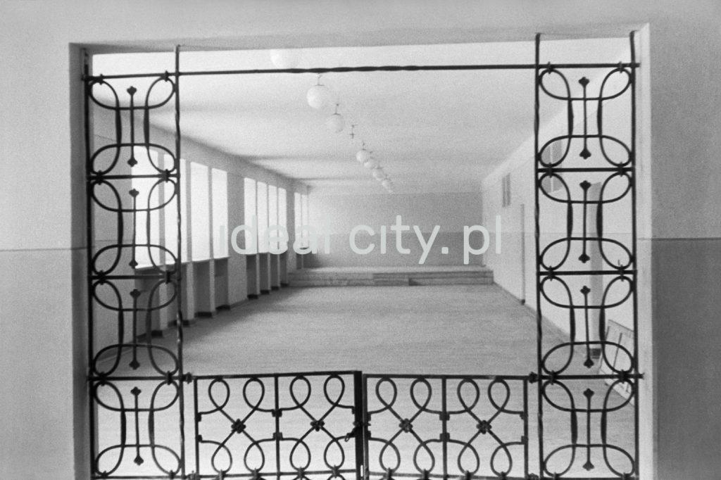 Widko na korytarz szkolny przez specjalnie projektowaną żelazną kratę