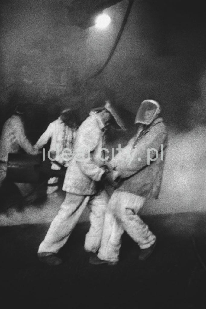 Dwa hutnicy w strojach wykonują prace przy Wielkim Piecu.