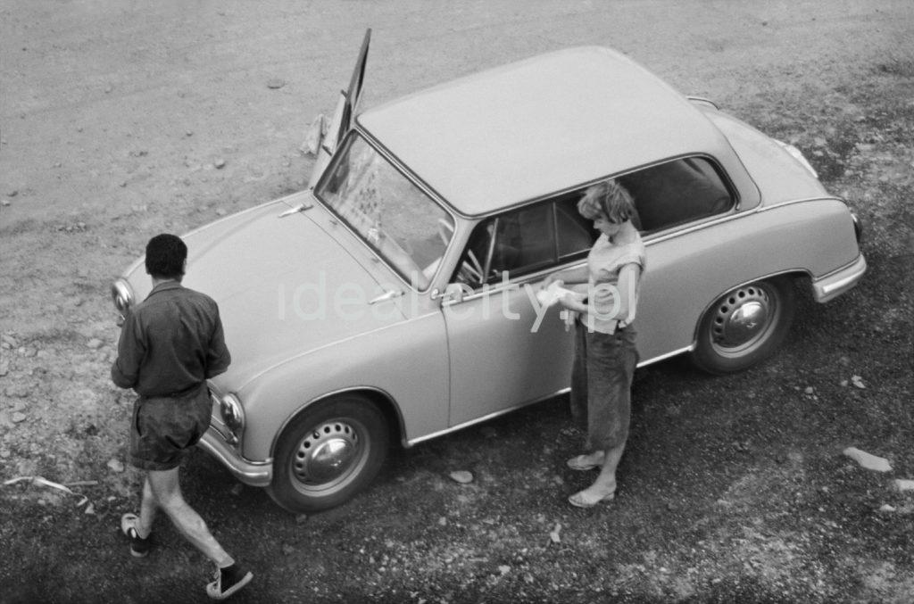 Dwie postaci krzątają się przy samochodzie.