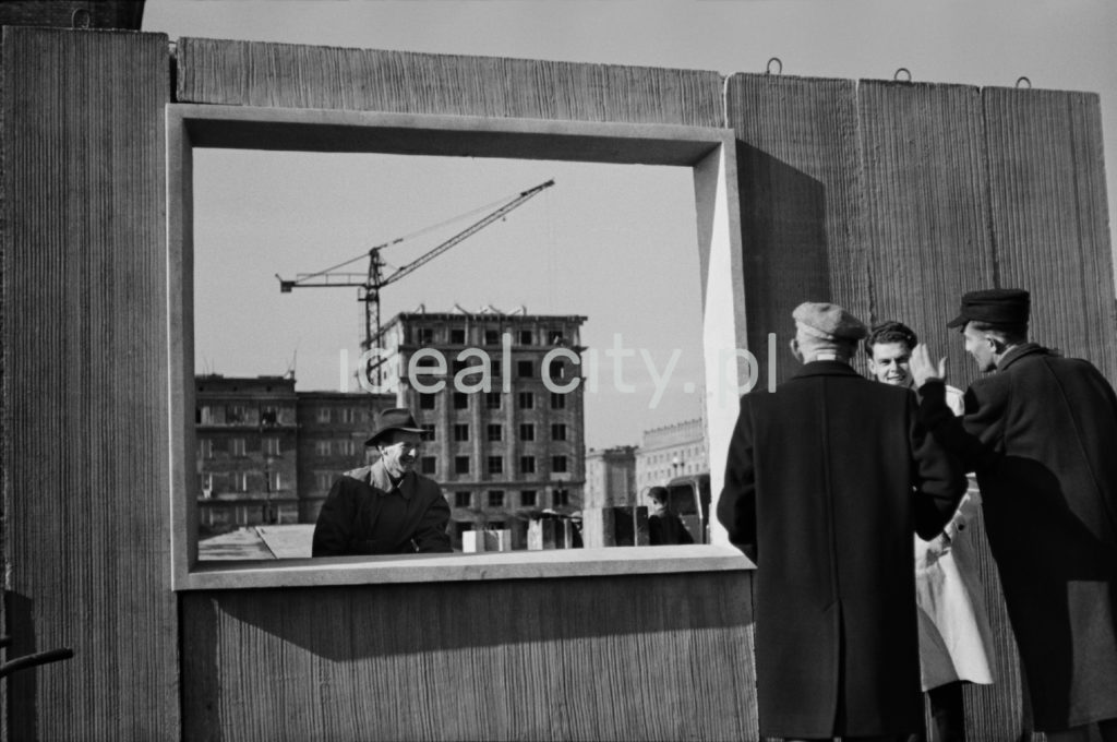 Mężczyźni w płaszczach dyskutują przy otworze okiennym w betonowej płycie.