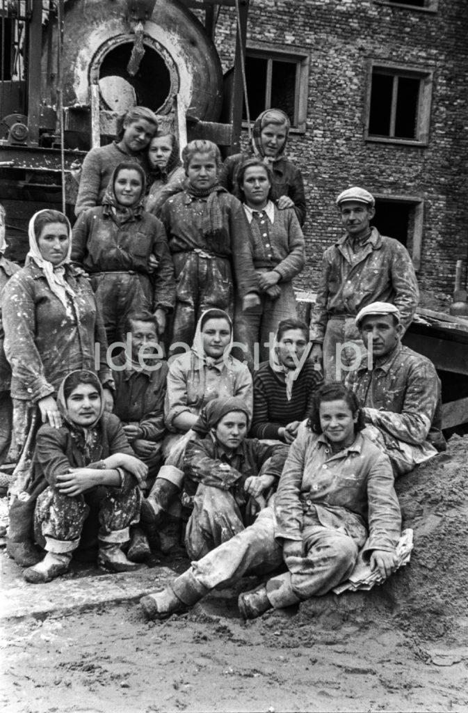 Kobiety i mężczyźni w zabrudzonych strojach roboczych pozują do zbiorowego zdjęcia przed budynkiem z cegły.
