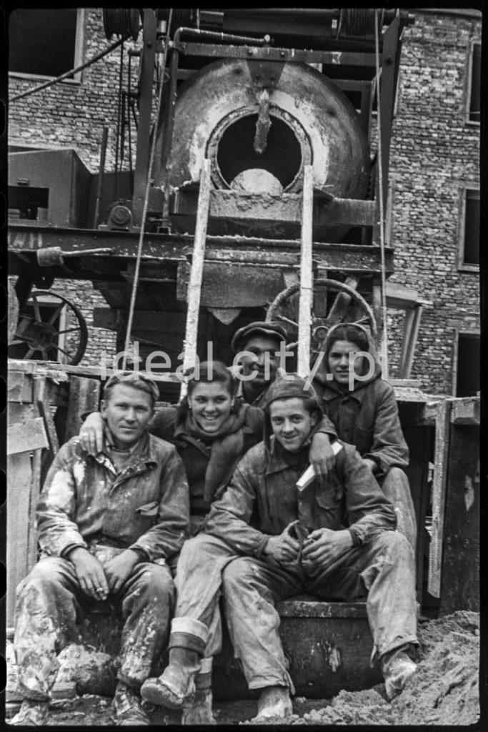 Mężczyźni i kobiety w zabrudzonych strojach roboczych pozują do zbiorowego zdjęcia przed budynkiem z cegły.