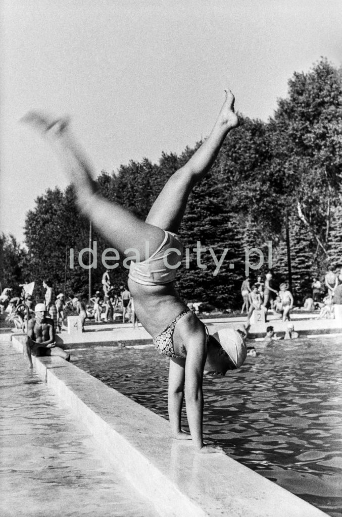 Pływaczka stoi na rękach na brzegu basenu.