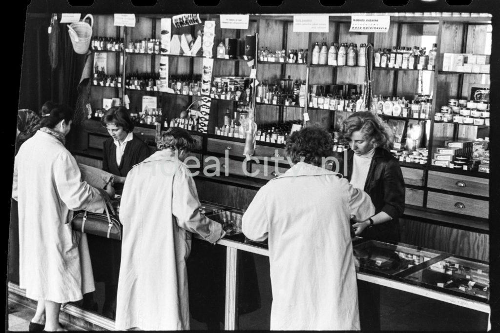 Kobiety w jasnych płaszczach stoją przed ladą sklepową.