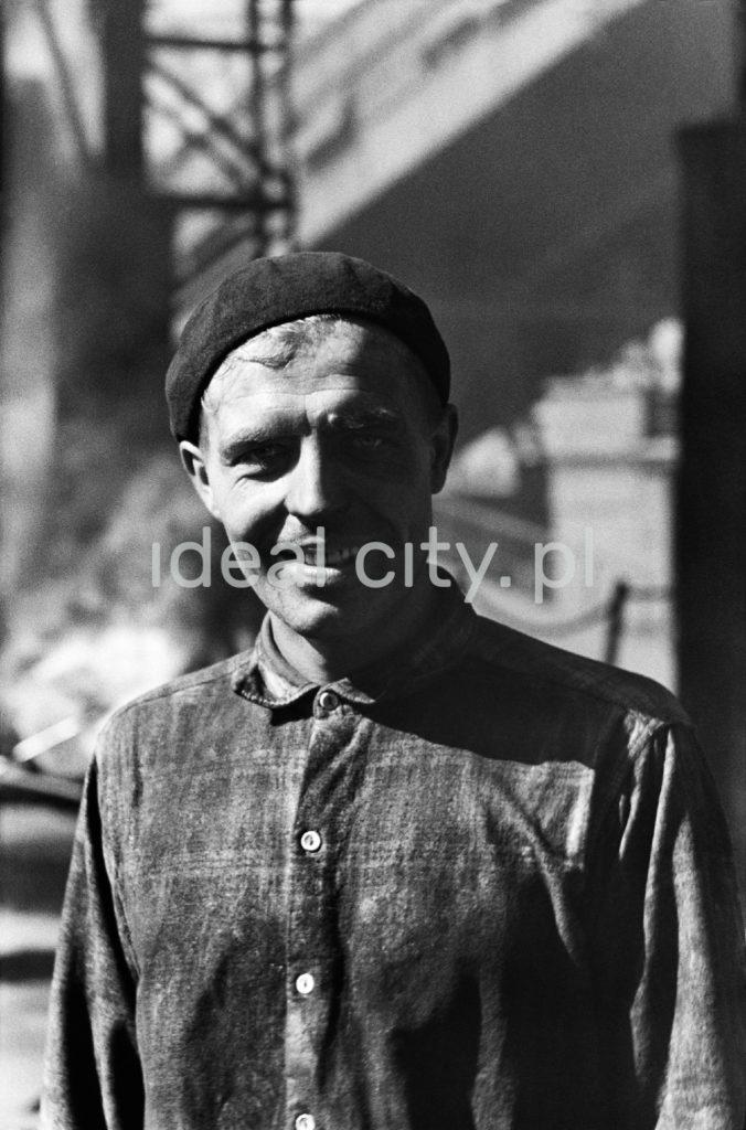 Portret uśmiechniętego robotnika w berecie na tle instalacji fabrycznych.