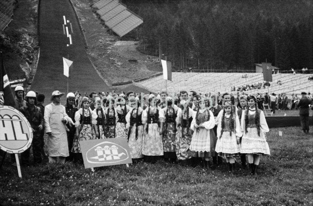 Młode kobiety w strojach ludowych pozują na tle skoczni narciarskiej.