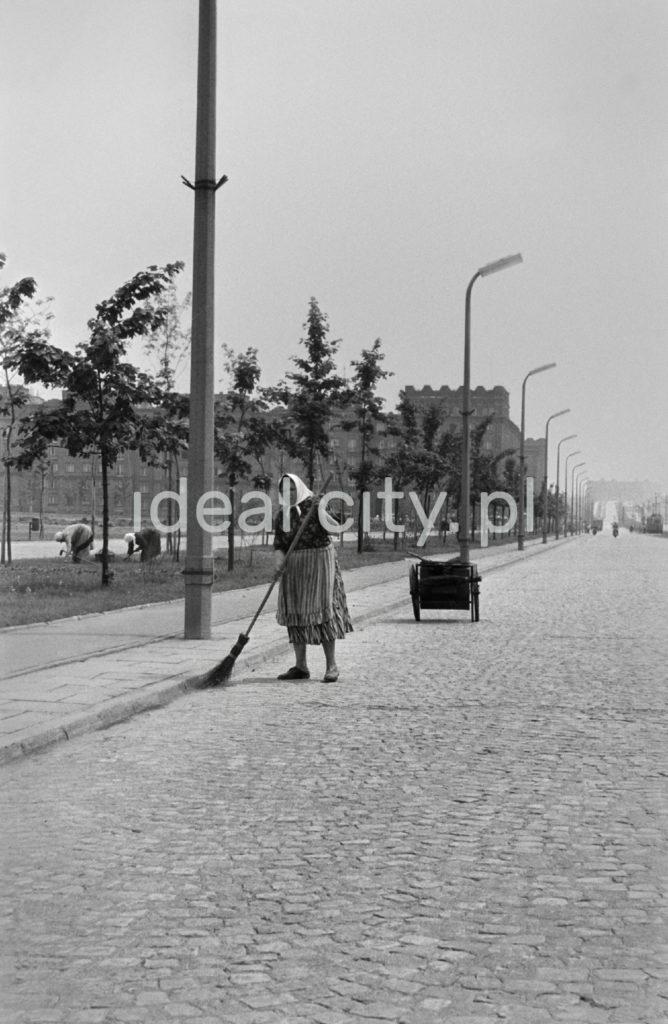 Kobieta zamiata ulicę, za nią wózek z narzędziami.