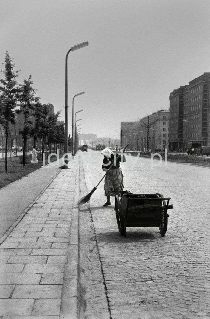 Kobieta zamiata ulicę, przed nią wózek z narzędziami.