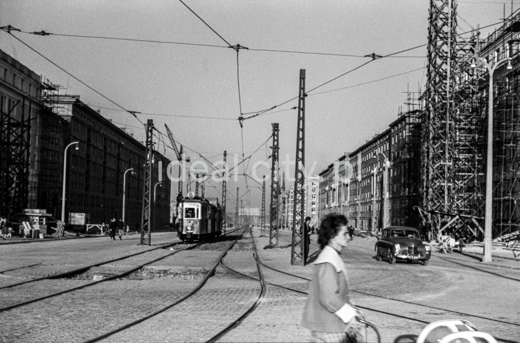 Ujęcie na szeroką aleję z linią tramwajową na środku, na pierwszym planie kontur kobiety prowadzącej wózek dziecięcy.