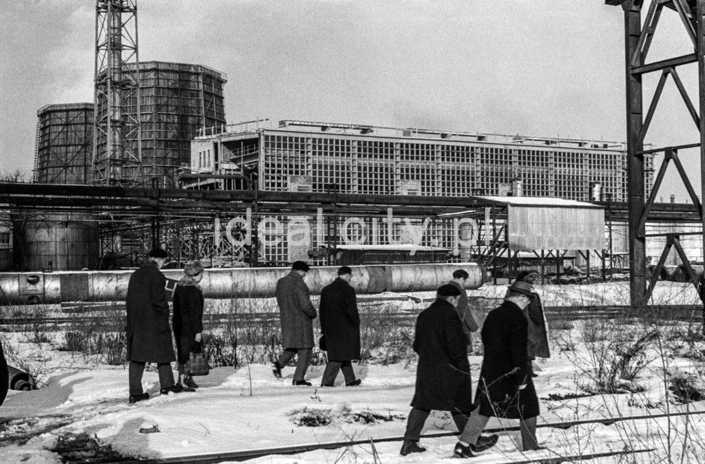 Urzędnicy w zimowych płaszczach kroczą grupą przez tereny fabryczne, ujęcie z tyłu.