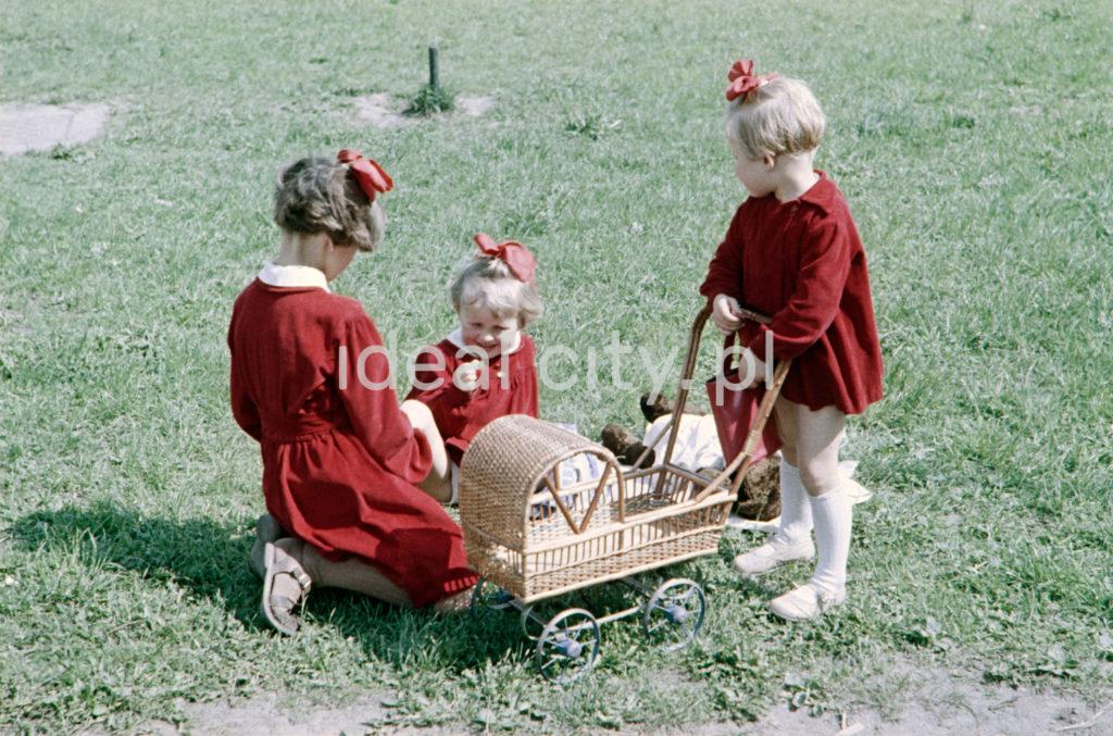 Dziewczunki w czerwonych sukienkach z wózkiem na lalki bawią się na trawie.