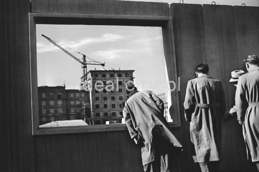 Trzech męźczyzn w płaszczach zagląda przez otwór okienny w prefabrykowanej ścianie, w tle budowa bloku mieszkalnego.
