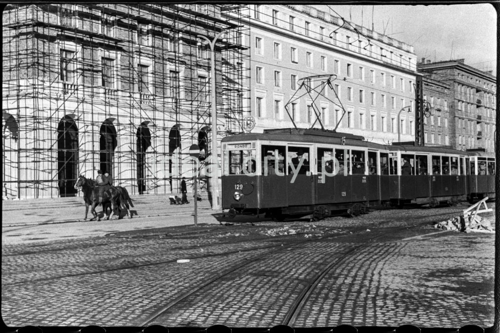 Wybrukowaną aleją jedzie tramwaj oraz jeździec na koniu, w tle finałowe prace tynkarskie przy socrealistycznej zabudowie mieszkalnej.