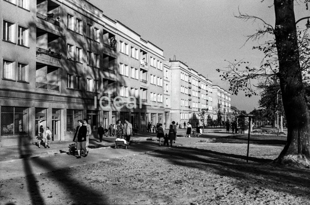 Ruch pieszy na szerokim chodniku przed ciągiem trzypiętrowych bloków mieszkalnych.