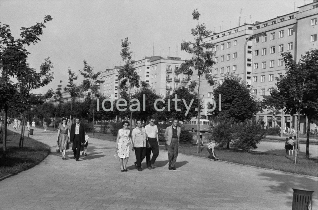 Ruch pieszy na szerokim deptaku miejskiego zieleńca, w tle zabudowa blokowa.