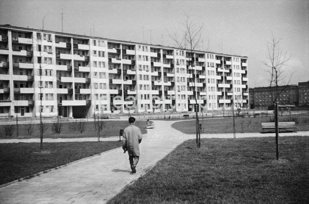 Mężczyzna w płaszczu idzie chodnikiem prowadzącym przez trawnik, w stronę długiego, niewysokiego bloku.