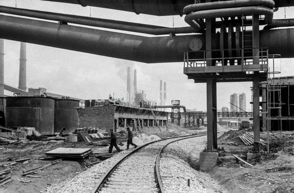 Postaci w strojach roboczych przechodzą przez tory prowadzące pomiędzy obiektami zabudowy fabrycznej.