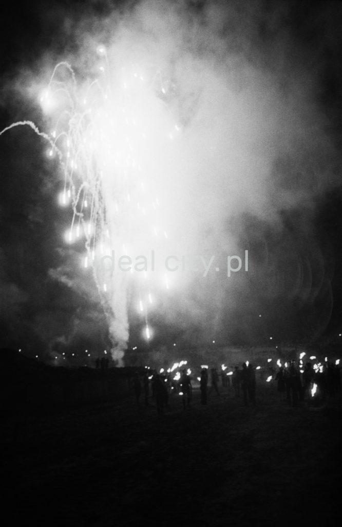 Tłum obserwuje nocą pokaz fajerwerków.