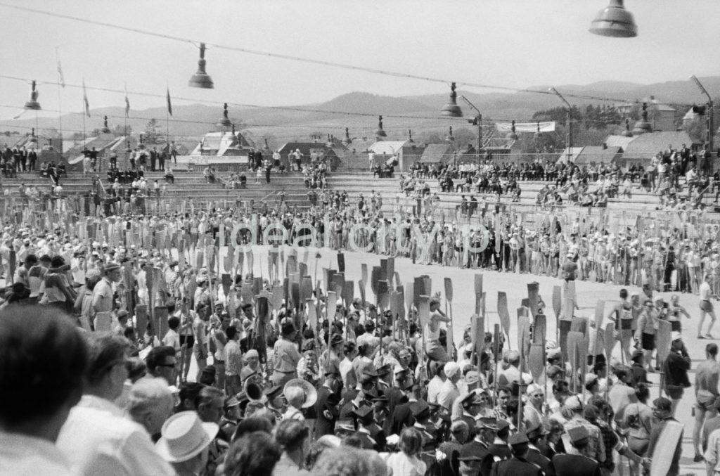 Tłum ludzi stoi na boisku z podniesionymi na sztorc wiosłami.