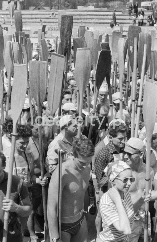 Tłum ludzi stoi z podniesionymi na sztorc wiosłami.
