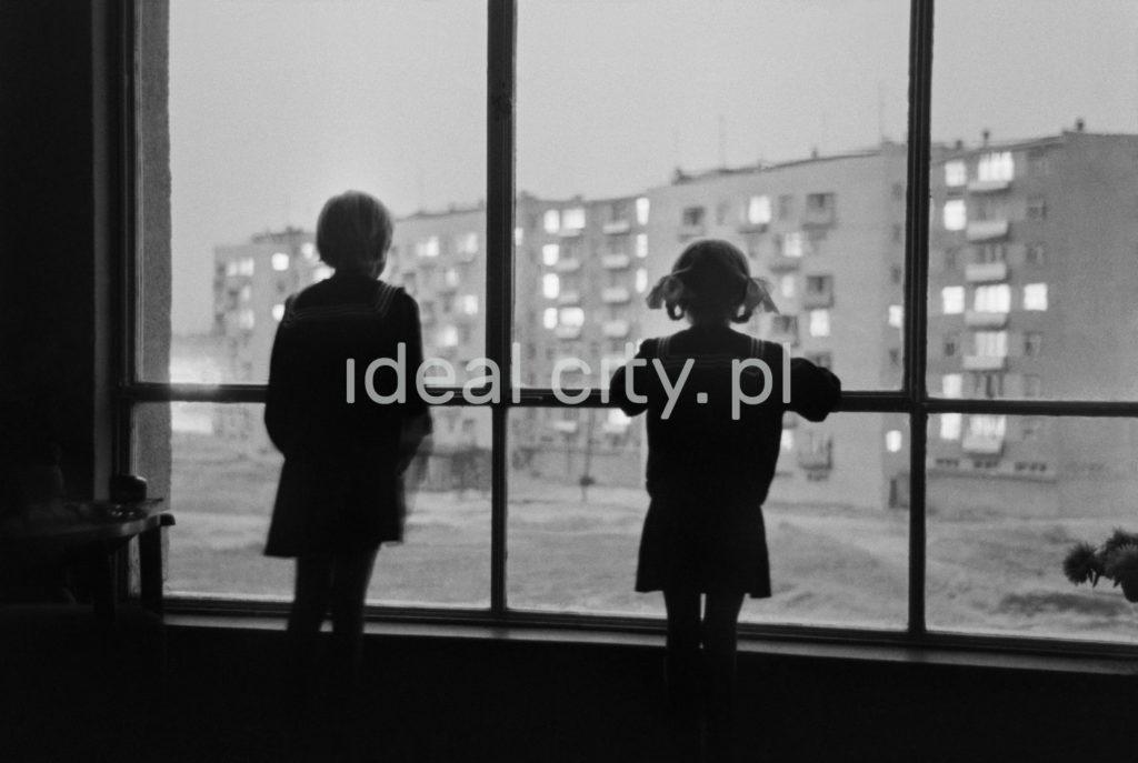 Kontury dwójki dzieci spoglądających z dużego okna na piętrze bloku mieszkalnego w stronę podwórka osiedla.