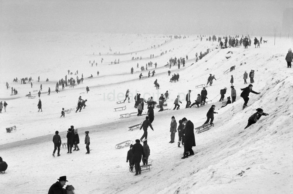 Perspektywiczne ujęcie na tłumy saneczkowiczów na pokrytej śniegiem skarpie.