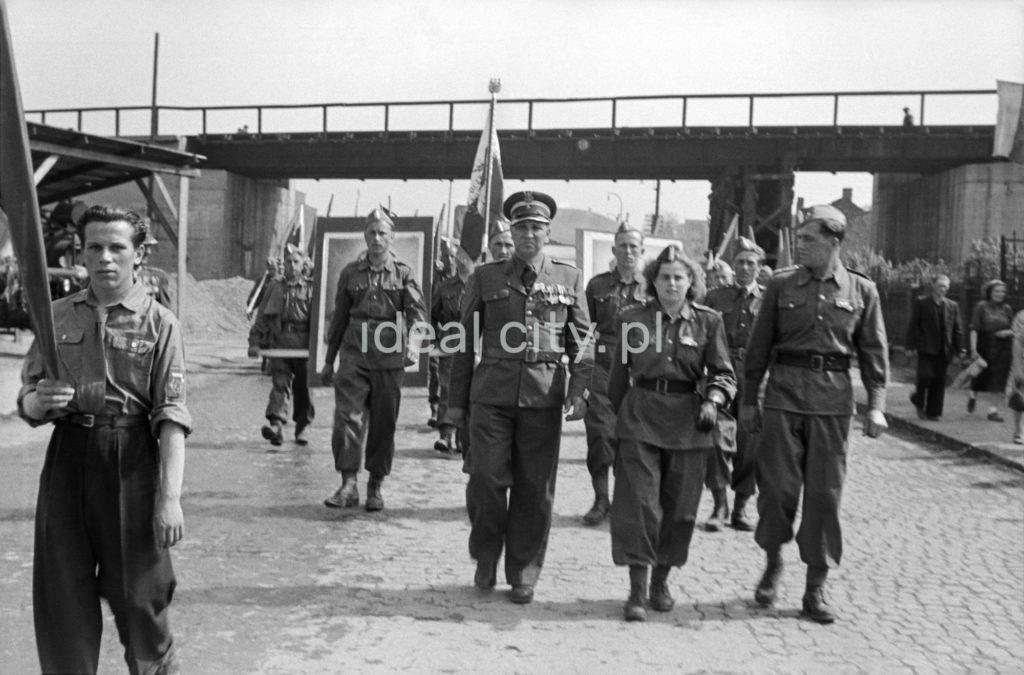 Mężczyźni i kobiety w mundurach maszerują w pochodzie.