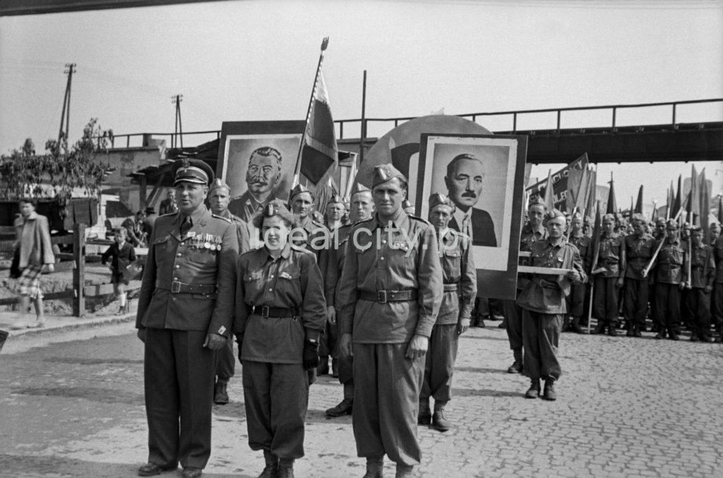 Mężczyźni i kobiety w mundurach maszerują w pochodzie, nad tłumem portrety Stalina i Bieruta.