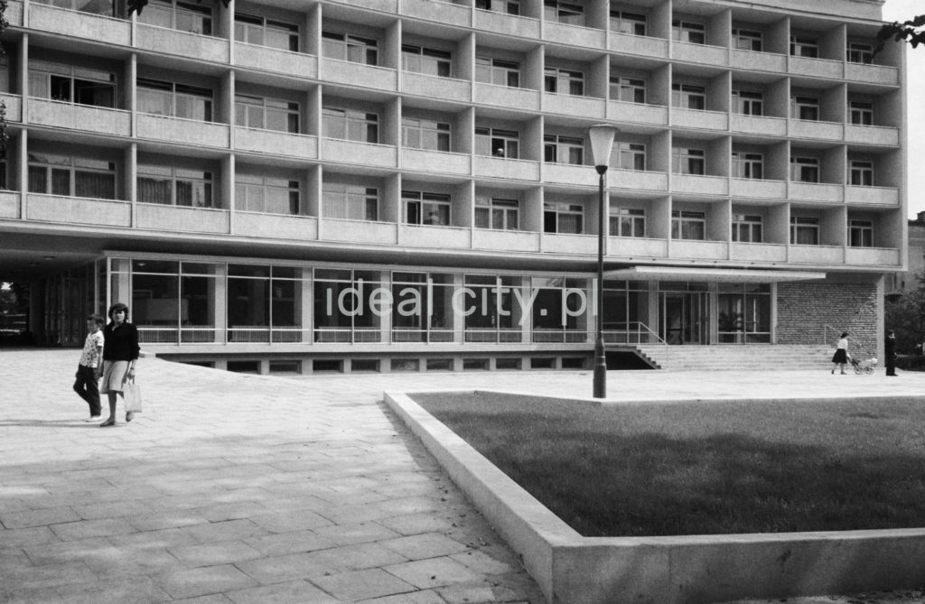 Matka z dzieckiem przechodzi przed bryłą modernistycznego hotelu.