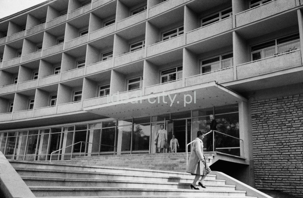 Kobieta schodzi po schodach przed modernistyczną bryłą hotelu.