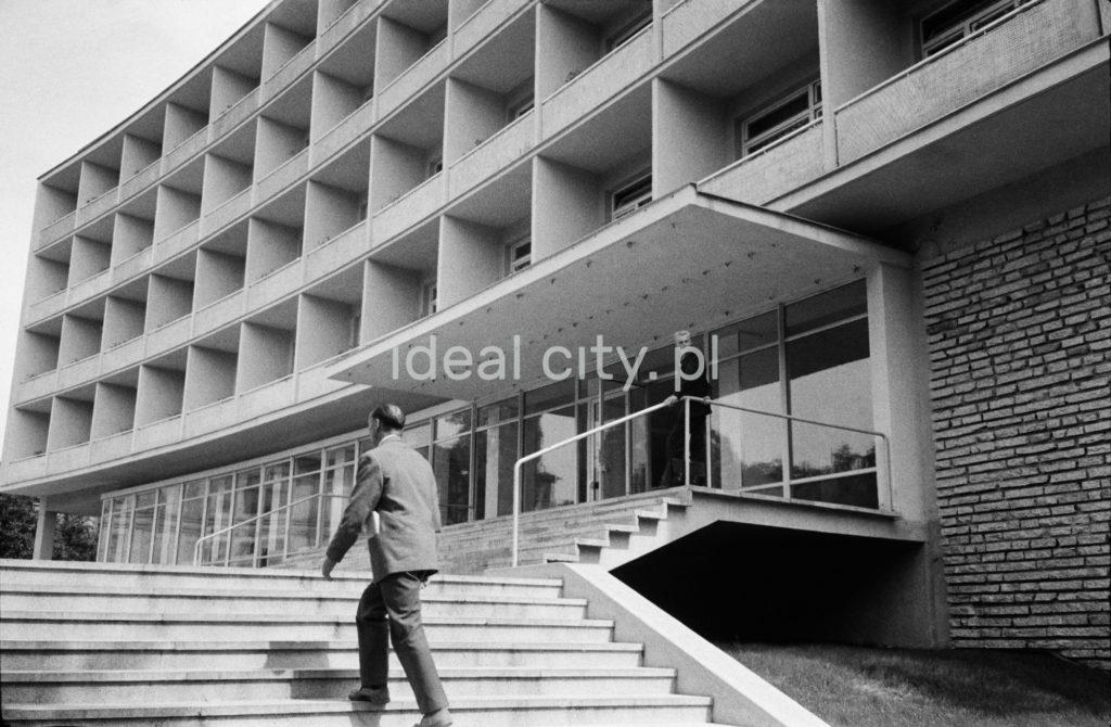 Mężczyzna w garniturze wychodzi po schodach przed modernistyczną bryłą hotelu.