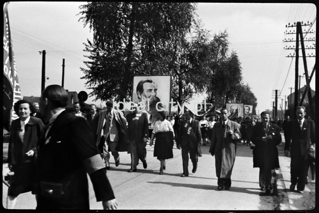 Odświętnie ubrani ludzie idą dynamicznie w pochodzie, w perspektywie ktoś niesie portret Engelsa.