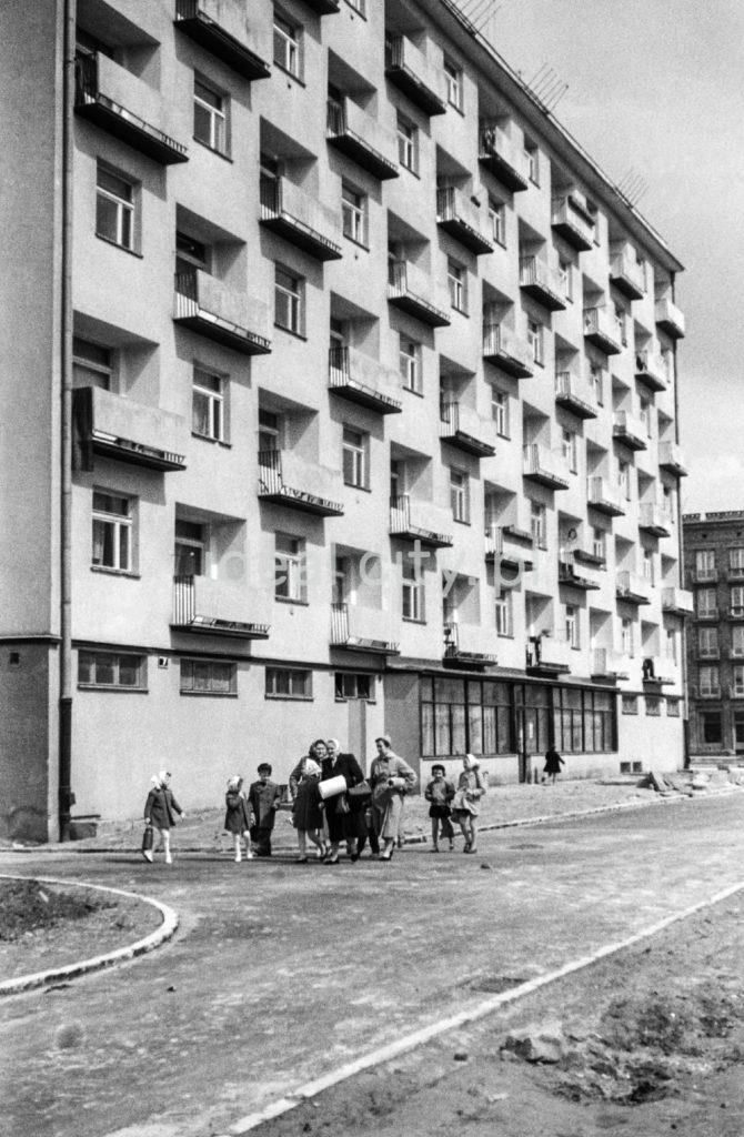 Matki z dziećmi przed blokiem z balkonami.